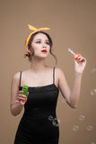 Playful pinup woman blowing party bubbles over yellow background Stock Image