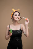 Playful pinup woman blowing party bubbles over yellow background Royalty Free Stock Photography