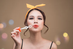 Playful pinup woman blowing party bubbles over yellow background Stock Images