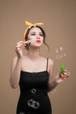Playful pinup woman blowing party bubbles over yellow background Stock Photos