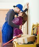 Playful plumber flirting with housewife Royalty Free Stock Images