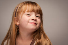 Playful Portrait of an Adorable Red Haired Girl on Grey Royalty Free Stock Images