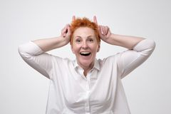 Playful pretty mature woman eith red hair shows horns Stock Images