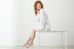 Playful pretty tender girl with curly red hair laughing posing sitting on table over white background. Copy space. Stock Image