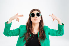 Playful pretty young woman in round sunglasses pointing on herself royalty free stock photography