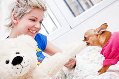 Playful puppy. Young blond woman playing with her pet Royalty Free Stock Image