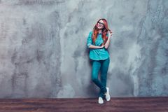 PLayful red hair foxy gorgeous girl in casual outfit is playing. With her hair on grey background. Ginger is stylish and looks spectacular Stock Photography