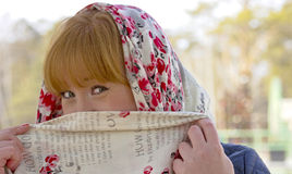 Playful red-haired girl closes half of his face with a scarf. Royalty Free Stock Image