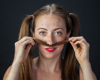 Playful Redhead. Funny portrait of a quirky girl playing with her pigtails Royalty Free Stock Images