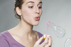 Playful 20's girl blowing soap bubbles for fun and imagination Stock Image