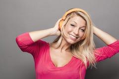 Playful 20s girl enjoying music on headphones Stock Images