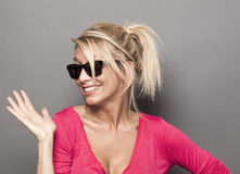 Playful 20s girl hiding behind her trendy sunglasses. Summer or star sunglasses concept - sophisticated young blonde woman acting like a star with smoked glasses Stock Photography