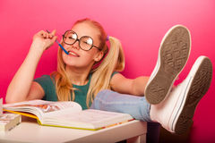 Playful schoolgirl with big eyeglasses concentrated thinking on royalty free stock images