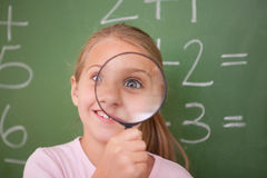 Playful schoolgirl looking through a glass royalty free stock image