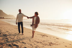 Playful senior couple on the beach Stock Photos