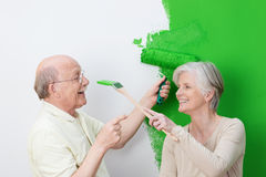 Playful senior couple painting their house green. With the men laughingly pointing a finger at his wife Stock Images