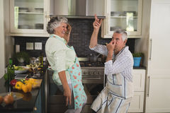 Playful senior couple spending leisure time in kitchen Royalty Free Stock Image