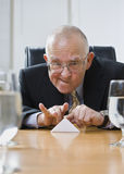 Playful senior male flicking paper. Royalty Free Stock Image