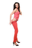 Playful sexy brunette in a red jeans Royalty Free Stock Images