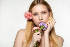 Playful and sexy portrait of pretty cheerful woman with spring flowers near her face, looking at the camera, isolated on royalty free stock image