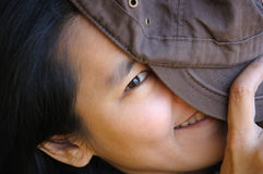 Playful shy woman hiding face with hat. Young Asian girl hiding face with hat Royalty Free Stock Photos