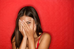 Playful shy woman hiding face laughing Royalty Free Stock Image