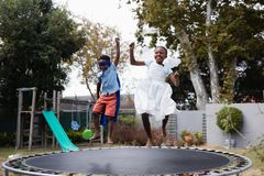 Playful siblings in costumes enjoying on trampoline Stock Photos