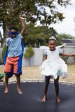Playful siblings in costumes jumping on trampoline Stock Photo