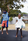 Playful siblings in costumes jumping on trampoline Royalty Free Stock Photography
