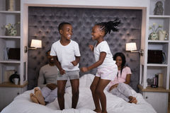 Playful siblings jumping on bed. At home Stock Photo