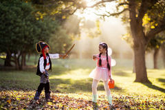 Playful siblings wearing costumes at park Royalty Free Stock Photography