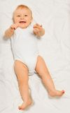 Playful small baby wearing white babygro laying. On the white blanket as a background stock images