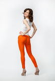 Playful smiling young woman in orange pants posing on neutral ba Stock Images