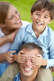 Playful son. Portrait of boy on fathers shoulders and laughing mother near by stock photo