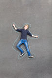 Playful teen boy. Lying on ground with lines drawn around him Stock Images