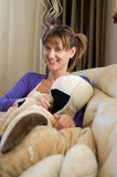 Playful Teen at Home Relaxing with her Dog. A young teen at home relaxing on the couch with her giant stuffed dog Royalty Free Stock Photo