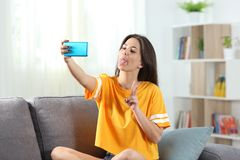 Playful teen taking selfies sitting on a couch. Playful teen joking taking selfies sitting on a couch in the living room at home Royalty Free Stock Photos