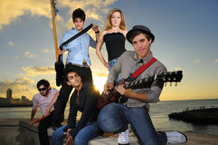 Playful teenage musical band posing at sunset. Portrait of young musical band with 4 boys and a girl posing outdoors at sunset with instruments Stock Photography