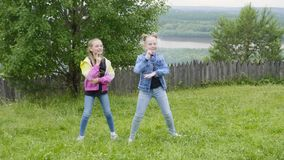 Playful teenager girls dancing on green meadow on forest and river landscape. Carefree girl teenagers having fun while stock video