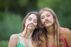 Playful teens with hair moustache. Playful teens girls with hair moustache royalty free stock photos