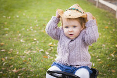 Playful Toddler Wearing Cowboy Hat and Playing on Toy Tractor Outside Royalty Free Stock Photos