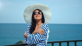 Playful travel fashion woman wearing white hat and sunglasses posing at horizon sea background. Medium shot. Beautiful stylish tourist female relaxing having stock footage