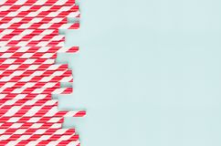 Playful trendy colors abstract background - red striped straws as border on mint paper backdrop. royalty free stock image