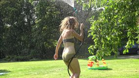 Playful wet woman girl refresh under water from hose in garden on hot summer day. 4K stock video