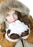 Playful winter girl holding snow. Playful young woman in winter coat with fur hood holding and tasting snow Royalty Free Stock Photos