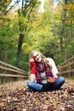 Playful woman in autumn. A happy young woman sitting on a path in fall playing with leaves stock photo