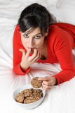 Playful woman breaking diet and eating cookie Royalty Free Stock Photography