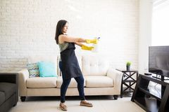 Playful woman cleaning living room with spray. Young modern woman in a playful mood wearing black apron and yellow latex gloves using spray as gun to clean Stock Photo