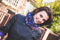 Playful woman in cloak and colored scarf Stock Photo