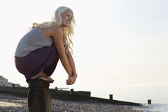 Playful Woman Crouching On Wooden Pole Royalty Free Stock Image